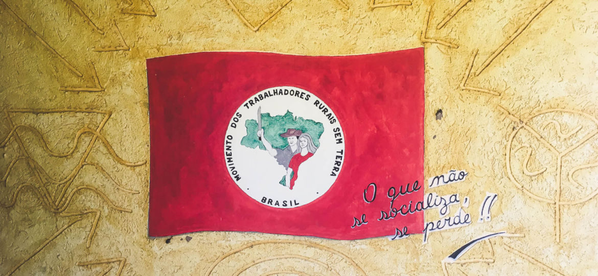 flag of the Brazilian Landless Workers' Movement laying on a clay background